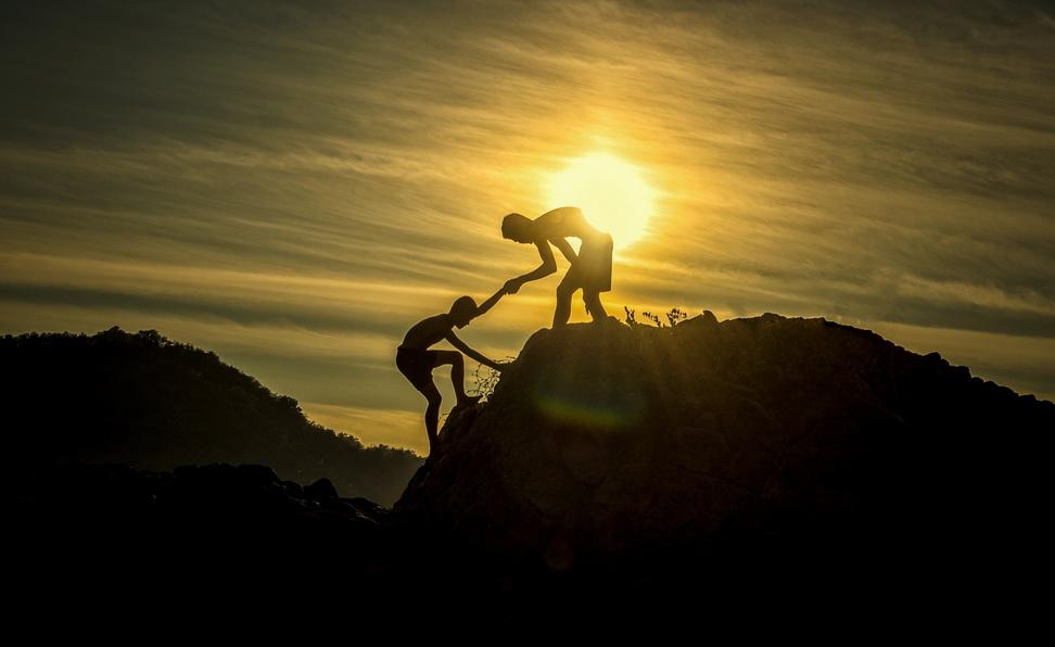 Homme qui en aide un autre à gravir une montagne.